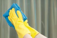 Vrouw in handschoenen die spiegel met vod schoonmaken Royalty-vrije Stock Afbeeldingen