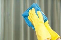 Vrouw in handschoenen die spiegel met vod schoonmaken Royalty-vrije Stock Afbeelding