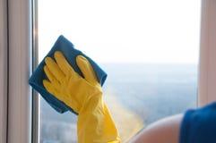 Vrouw in handschoenen die venster met vod schoonmaken Stock Afbeeldingen
