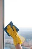 Vrouw in handschoenen die venster met vod schoonmaken Stock Afbeelding