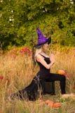 Vrouw in heksenkostuum het praktizeren yoga Stock Foto's