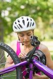 Vrouw in helm die ketting op bergfiets proberen te bevestigen Royalty-vrije Stock Fotografie