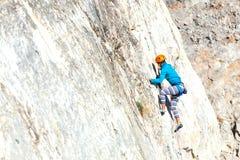 Vrouw in helm op de rots Stock Afbeeldingen