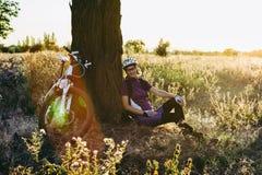 Vrouw in helmzitting bij zonsondergang dichtbij haar fiets royalty-vrije stock afbeeldingen