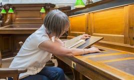 Vrouw het Aanpassen Boeksteun in Bibliotheek Royalty-vrije Stock Fotografie
