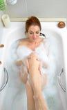 Vrouw het baden met heel wat schuim Royalty-vrije Stock Afbeeldingen