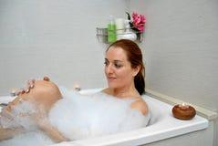 Vrouw het baden met heel wat schuim Stock Foto