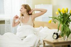 Vrouw in het bed stock foto
