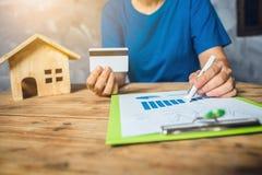 Vrouw het berekenen de huisbelasting financieel voor koopt een nieuwe huisbegroting Stock Afbeeldingen