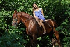 Vrouw het berijden paard bareback door bos Stock Afbeelding