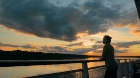 Vrouw het bewonderen zonsondergang van dek van cruiseschip stock videobeelden