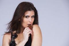 Vrouw het bijten chocolade stock fotografie