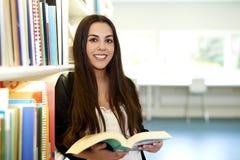 Vrouw in het boek van de bibliotheeklezing Stock Foto's