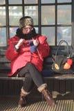 Vrouw het breien op een bank stock foto's