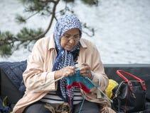 Vrouw het breien op een dag van bank outsideon multiculture in Holland Royalty-vrije Stock Foto