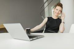 Vrouw in het bureau Stock Afbeeldingen