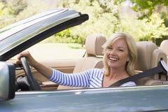 Vrouw in het convertibele auto glimlachen Stock Foto's