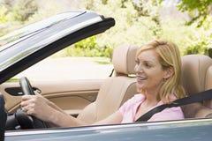 Vrouw in het convertibele auto glimlachen Stock Afbeelding
