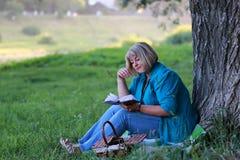 Vrouw in het de lezingsboek van de parkboom Stock Afbeeldingen