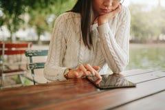 Vrouw het doorbladeren websitepagina's op aanrakingsstootkussen Stock Foto's