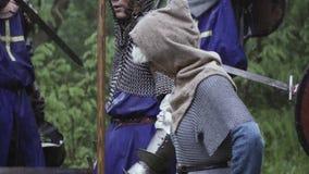 Vrouw het dragen chainmail bevindt zich met de militairen op het slagveld stock video