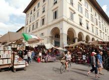 Vrouw het drijven door cyclus voorbij grote openluchtmarkt met kleding in centrum van oude stad stock foto