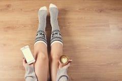 Vrouw het drinken cappuccinokoffie en het zitten op de houten vloer Sluit omhoog van vrouwen` s handen houdend kop van slimme kof Royalty-vrije Stock Foto