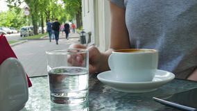 Vrouw het drinken koffie De glazen met water zijn dichtbij de kop stock footage