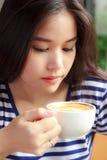 Vrouw het drinken koffie in een koffie stock foto
