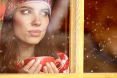 Vrouw het drinken koffie en het kijken uit het venster op de winter DA Royalty-vrije Stock Foto