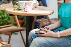 Vrouw het drinken koffie en het lezen van boek in een openluchtkoffie Royalty-vrije Stock Foto's