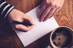 Vrouw het drinken koffie en het schrijven brieven royalty-vrije stock fotografie