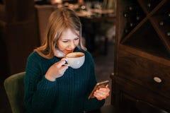 Vrouw het drinken koffie en met smartphone het in hand glimlachen in koffie royalty-vrije stock fotografie