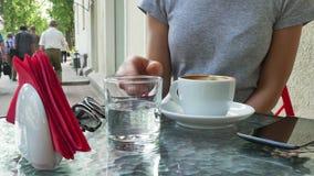 Vrouw het drinken koffie Glazen met water stock footage