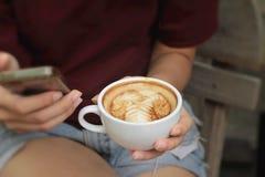 Vrouw het drinken koffie in kop en slimme telefoons stock foto's