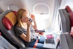 Vrouw het drinken koffie op commercieel passagiersvliegtuig tijdens vlucht royalty-vrije stock fotografie