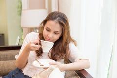 Vrouw het drinken koffie op de bank Royalty-vrije Stock Foto's