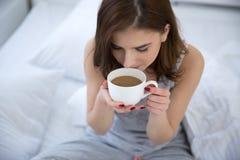 Vrouw het drinken koffie op het bed royalty-vrije stock foto