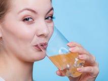 Vrouw het drinken sinaasappel op smaak gebracht drank of sap Stock Foto