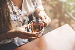 Vrouw het drinken thee bij koffie met zonsopgang die binnen door venster stromen en tot gloed leiden in de lens, en vrouwenhand stock afbeelding