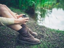Vrouw het drinken thee door vijver in bos Stock Afbeeldingen