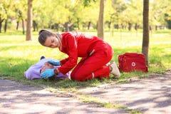 Vrouw in het eenvormige controleren ademhaling van de onbewuste mens in openlucht stock afbeelding