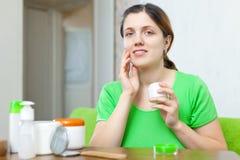 Vrouw in het groene geven voor haar gezicht Stock Foto