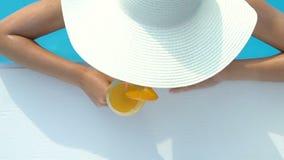 Vrouw in het grote hoed zwemmen en het drinken cocktail bij poolbar, het kuuroord van de luxetoevlucht stock video