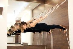 Vrouw het hangen op drooglijn parallel met het grondgezicht die neer yoga op zwangerschapsstrepen in de gymnastiek uitoefenen Pas royalty-vrije stock afbeelding