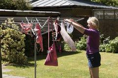 Vrouw het hangen te drogen uitwassen Stock Foto's