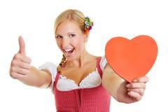 Vrouw in het hart en de duimen van de dirndlholding omhoog Stock Foto