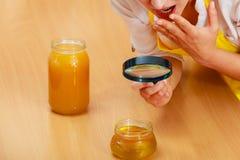 Vrouw het inspecteren honing met vergrootglas Stock Afbeelding