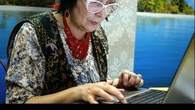 Vrouw, het Kaukasische behoren tot een bepaald ras, in oogglazen die iets zitten die op haar computertoetsenbord typen stock videobeelden
