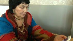 Vrouw, het Kaukasische behoren tot een bepaald ras, in oogglazen die, met iemand zitten die met haar smartphone spreken stock footage